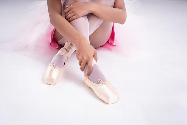 La mano de la dama está tocando el zapato de ballet de satén con la mano derecha,