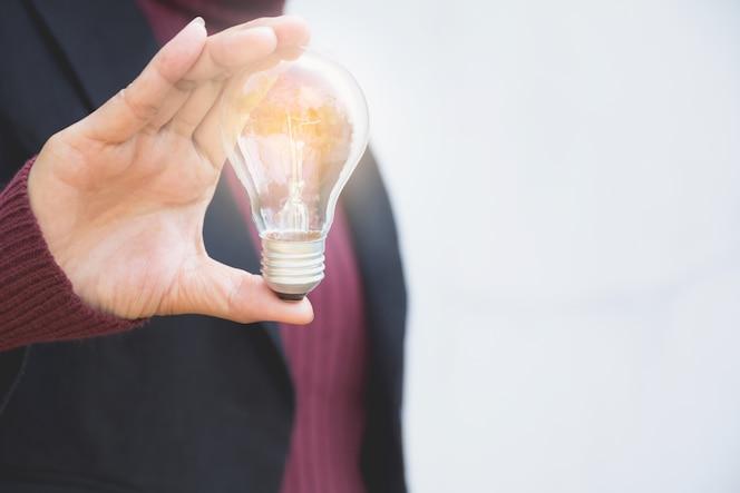 Mano de businesswomean sosteniendo la bombilla para la idea o el éxito o la energía solar