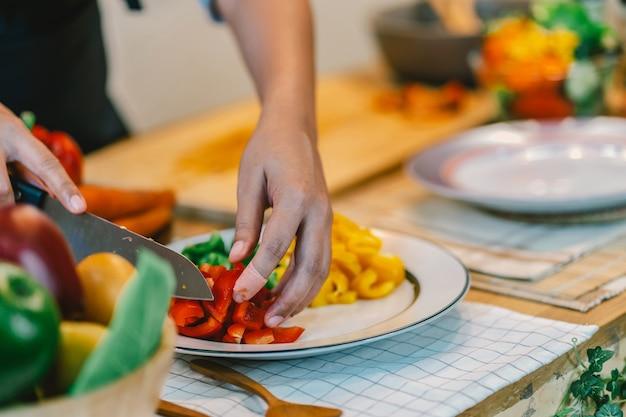 Mano de chef de primer plano cortar el pimiento en la tabla de cortar en la cocina moderna
