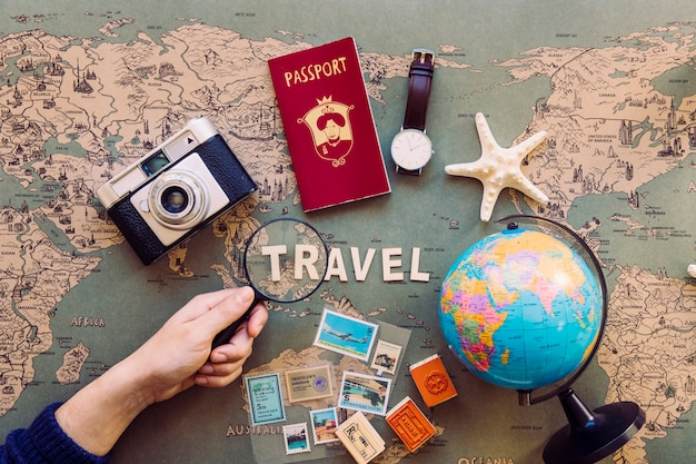 Mano de cultivo con lupa sobre escritura de viaje