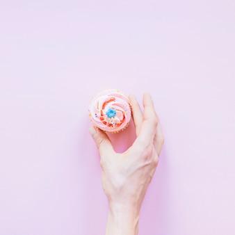 Mano de cultivos con cupcake de cumpleaños