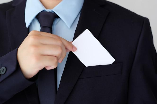 Mano de hombre de negocios que sostiene la tarjeta de visita blanca en blanco con el espacio de la copia para el texto, parte posterior del negocio
