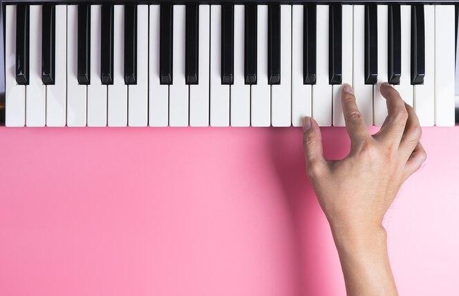Mano de jugador de teclado está jugando en el teclado con espacio de copia de color rosa