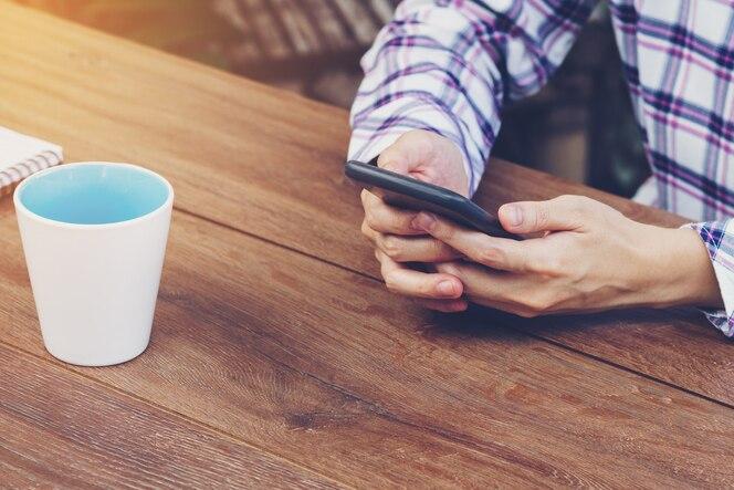 Mano de la mujer de asia que sostiene y que usa el teléfono en cafetería.