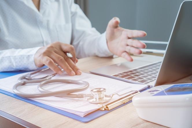 Mano de médico de medicina explicando al paciente en el consultorio, trabajando en la computadora portátil