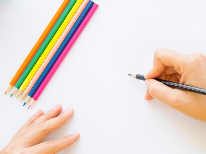 Mano de mujer con lápiz escribiendo en papel blanco.
