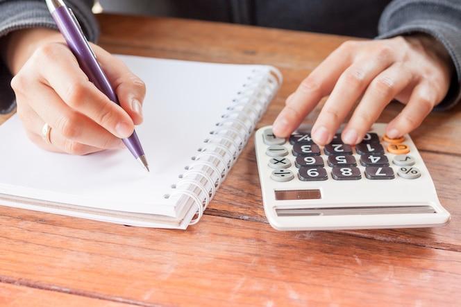 Mano de mujer con pluma escribiendo en el cuaderno