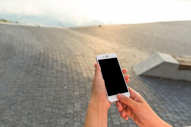 Mano de mujer con teléfono celular al aire libre