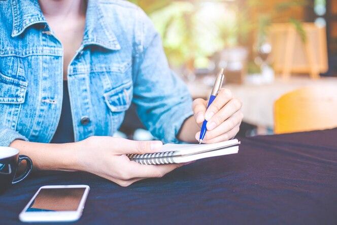 Mano de mujer está escribiendo en un bloc de notas