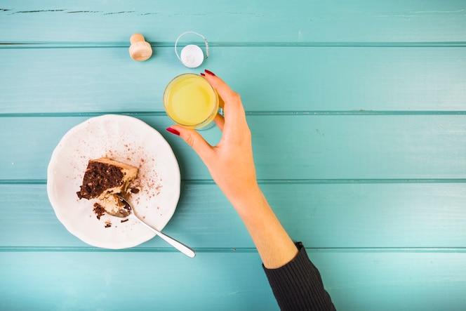 Mano de mujer sosteniendo la bebida con pasteles en la mesa