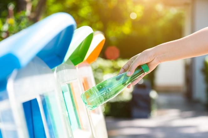 Mano de mujer sosteniendo y poniendo residuos de botellas de plástico en la basura