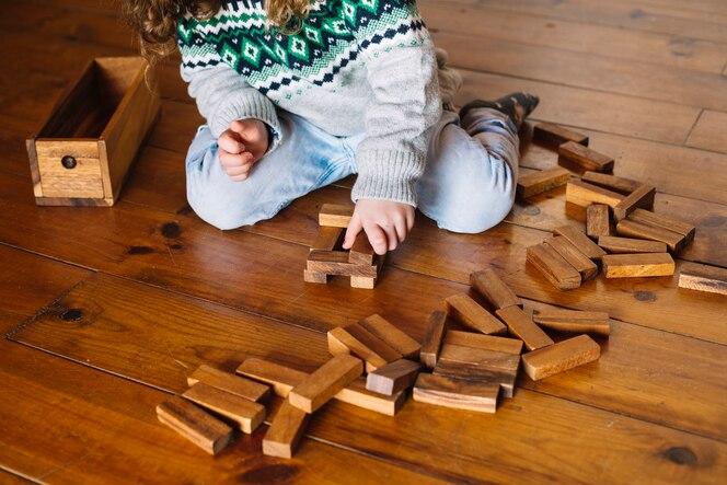 Mano de niña jugando juego de bloque de madera en casa
