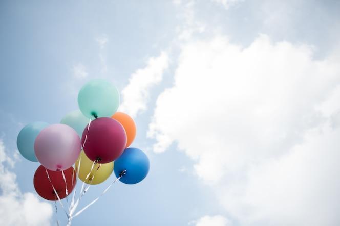 Mano de niña sosteniendo globos de colores