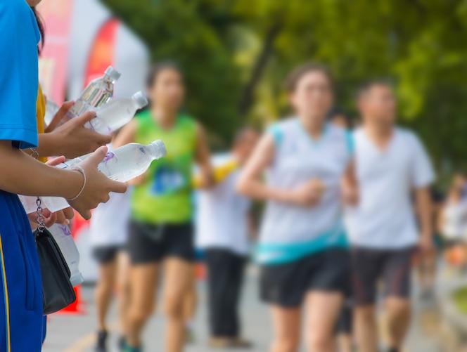 Mano de un voluntario dando agua corredores de maratón corriendo en la calle
