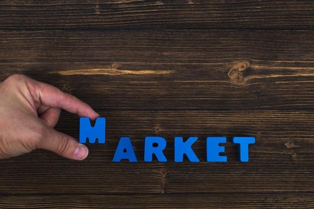 Mano y dedo arreglan letras de texto de la palabra mercado