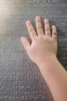 La mano y los dedos del niño ciego tocando las letras braille en la placa de metal