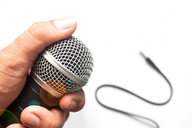 Mano del hombre con micrófono sobre fondo blanco