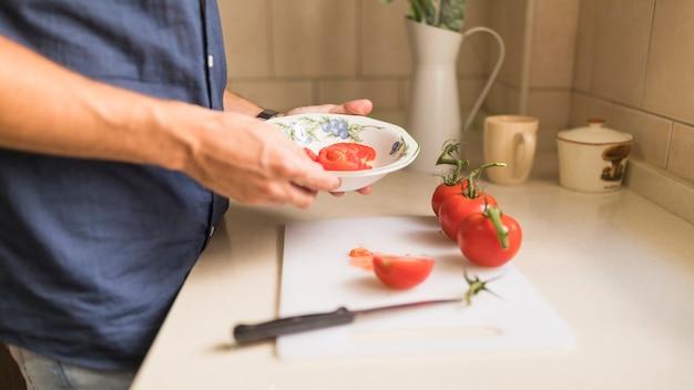 Mano del hombre con rodaja de tomate en el tazón