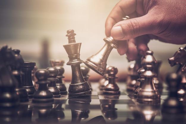 Mano del hombre de negocios que mueve la figura del ajedrez en el juego de éxito de la competencia.