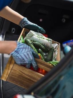 Mano del jardinero guardando la caja de verduras en el baúl del auto