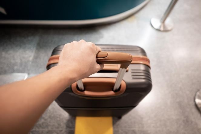 Mano del viajero que sostiene la maleta en un aeropuerto.
