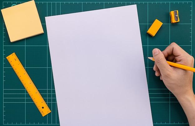 Mano derecha con lápiz prepararse para escribir en papel sobre alfombra de corte