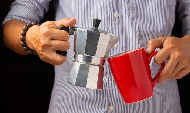 La mano derecha sostiene la cafetera y la otra mano sostiene la taza de café roja.