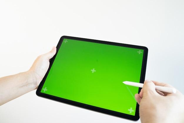 Mano dibuja un lápiz en una tableta con un chromakey en la pantalla.