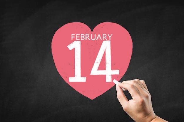 Mano dibujando un corazón con el 14 de febrero