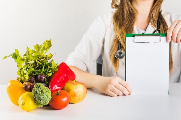 La mano del dietista femenino que sostiene el tablero en blanco con la comida sana en el escritorio
