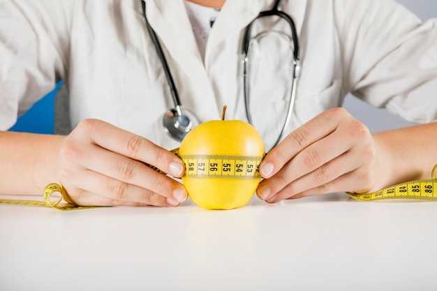 Mano de dietista sosteniendo manzana con cinta métrica