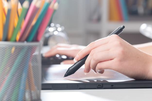 Mano del diseñador con un bolígrafo en una tableta