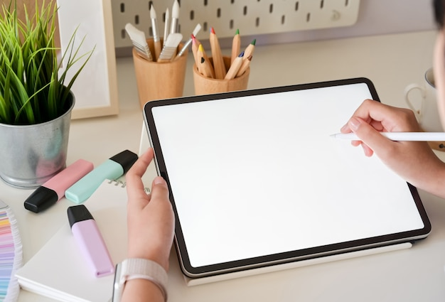 Mano del diseñador gráfico usando la pluma digital de la tableta en estudio