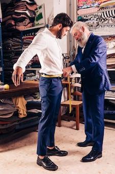 La mano del diseñador de moda masculino mayor que toma la medida de la cintura de su cliente con cinta métrica amarilla