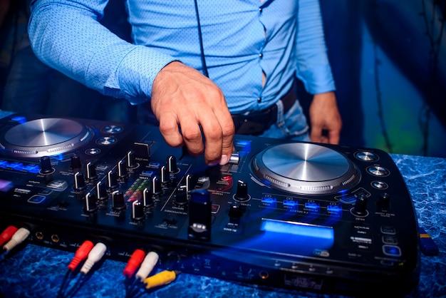 La mano de dj controla el volumen y mezcla música en un mezclador profesional en una discoteca en una fiesta
