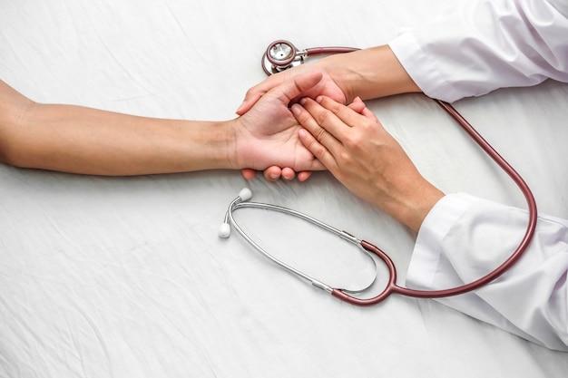 Mano del doctor que tranquiliza a su paciente femenino