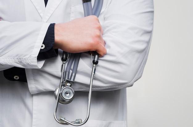 La mano de un doctor de sexo masculino que sostiene el estetoscopio disponible contra el contexto blanco