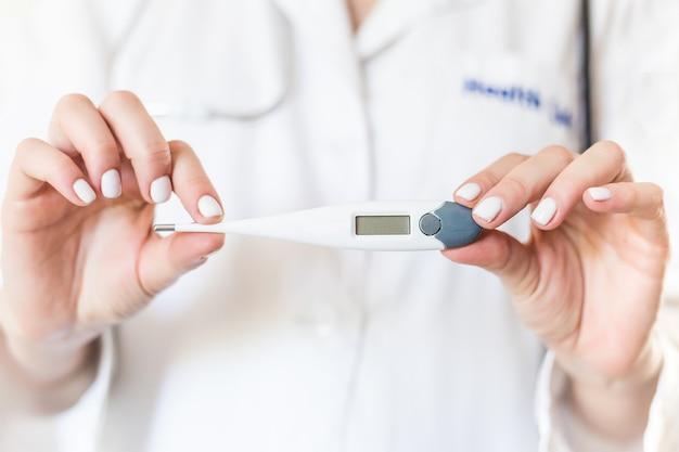 Mano del doctor sosteniendo termómetro electrónico, primer plano