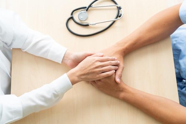 Mano de la doctora sosteniendo a su paciente senior