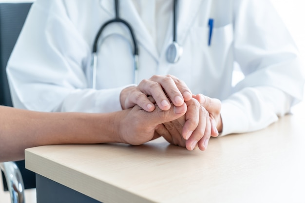 Mano de doctora sosteniendo a su paciente senior