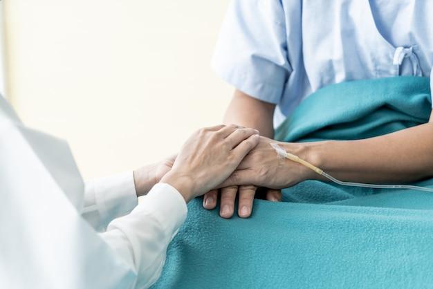 Mano de doctora tranquilizadora sobre su paciente senior