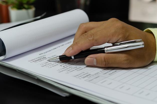 Mano con documentos de aplicación de escritura de pluma en el escritorio.