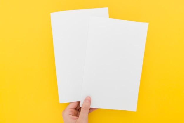 Mano con dos folletos