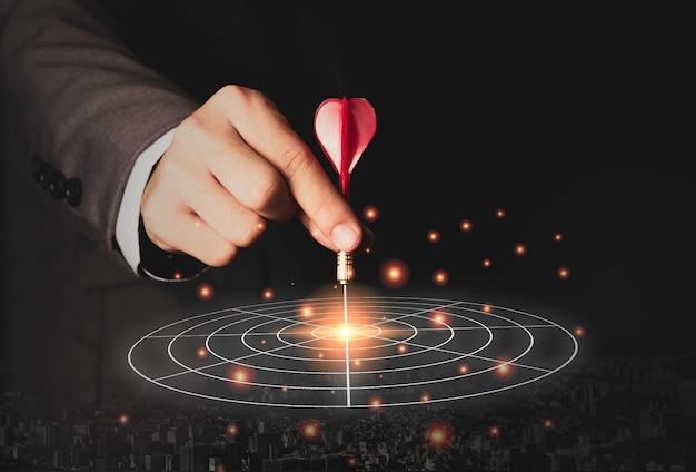 Mano ejecutiva de marketing con dardo rojo puesto en el centro del tablero de destino. objetivo de inversión empresarial y concepto objetivo.