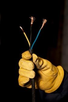 Mano de electricista con guantes mostrando cables