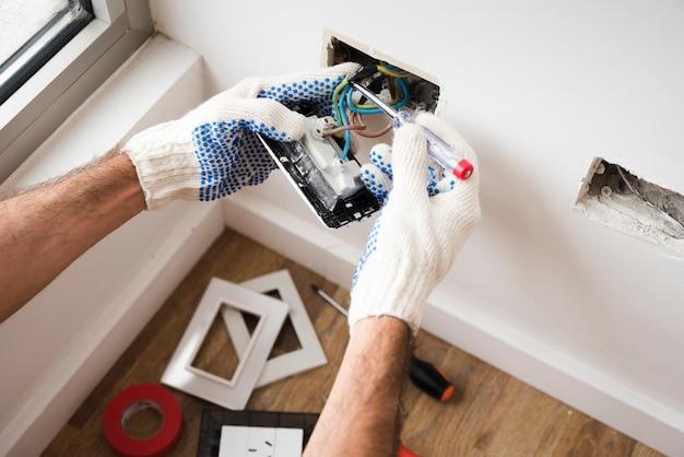 Mano de electricista instalando toma de corriente en casa.
