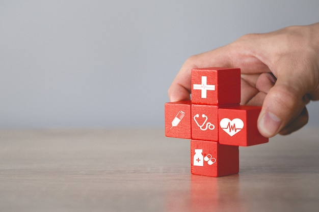 Mano elegir cubo de madera con icono médico, concepto de seguro.