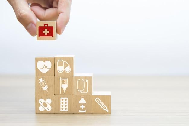 Mano elegir iconos de bolsa de primeros auxilios en bloque de madera