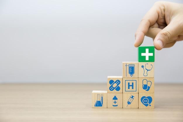 Mano elegir médico y salud en bloques de madera.