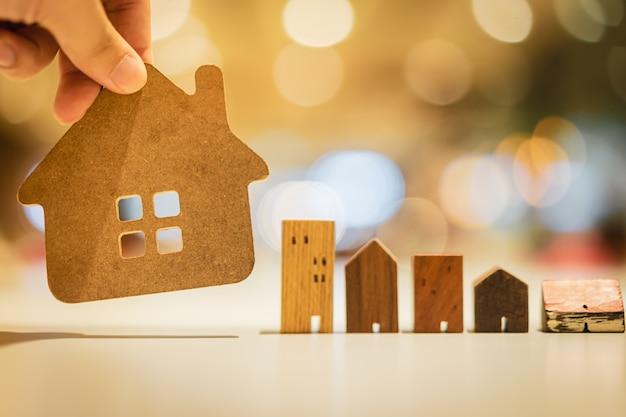 Mano elegir mini modelo de casa de madera del modelo en la mesa de madera,